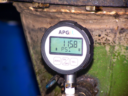 A digital absolute pressure gauge on the discharge nozzle of a pump