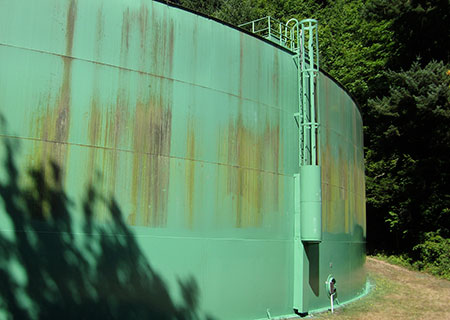 a green water tank in the forest