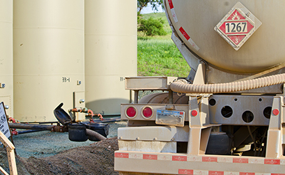 An oil tanker truck pumps oil from containment tanks, in an API 18.2-related scenario